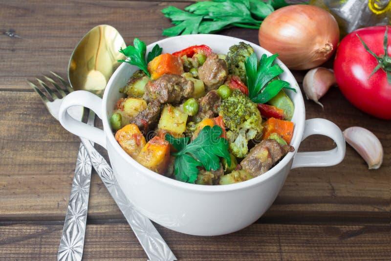 Tjänat som nötköttkött lät småkoka med grönsaker i keramisk kruka med ingredienser på träbakgrund royaltyfri foto