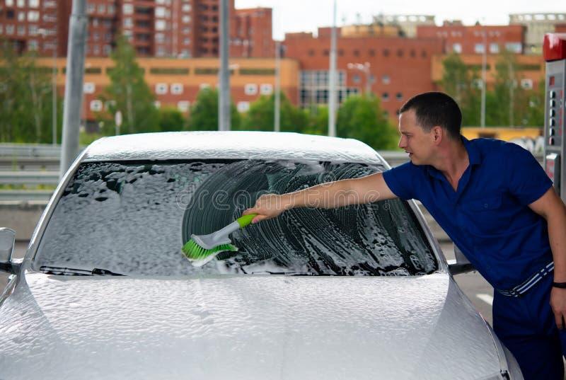 tjänste- arbetare för bil, washes exponeringsglaset med en borste med skum arkivfoton