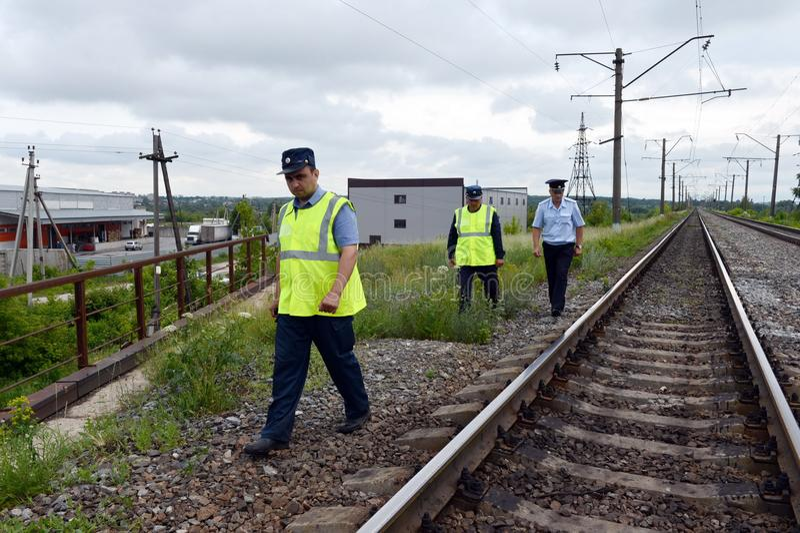Tjänstemän av avdelnings- säkerhet med en polis kopplar förbi avsnittet av järnvägen arkivbild
