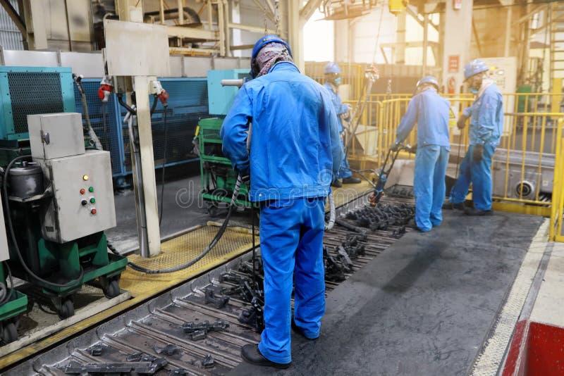 Tjänstemän bär blåa arbetskläderhjälmar och säkerhetsskor med personlig skyddsutrustning Använd tillfångatagandehjälpmedlet och a royaltyfri bild