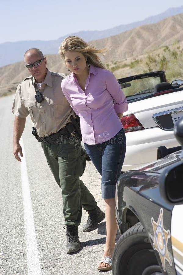 Tjänsteman Arresting Young Woman royaltyfri foto