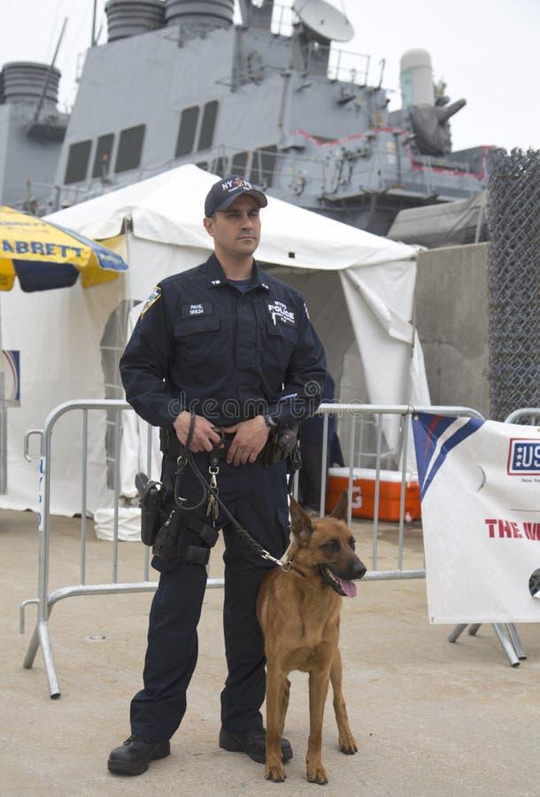 Tjänsteman för NYPD-räknareterrorism med den belgiska herden som ger säkerhet under den hastiga veckan 2014 royaltyfri foto
