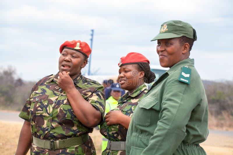 Tj?nsteman f?r tre afrikansk kvinnor i r?d basker och gr?n likformig av Umbutfo Swaziland f?rsvarstyrka USDF royaltyfria foton