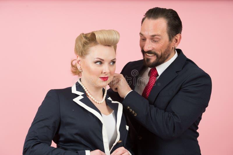 Tjänstemanpar som flörtar sig mantagande på vita perls på flickor hånglar Grabbblickar in i det kvinnliga bröstet royaltyfria bilder