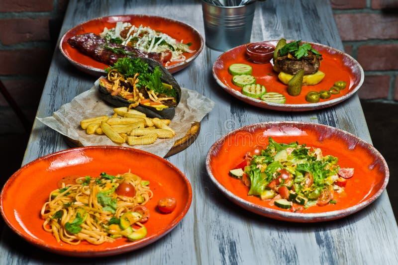 Tj?nad som tabell med olik disk av restaurangen Varmkorv, grillfestgrisk?ttst?d, biff, Carbonara deg och krabbasallad Slapp fokus arkivbild