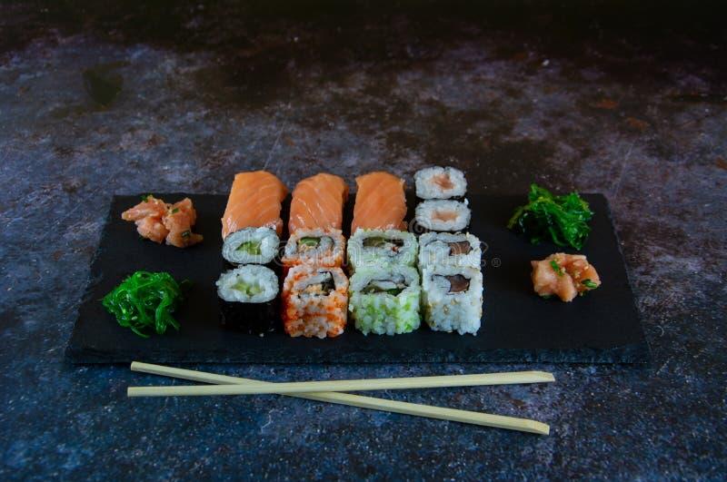 Tj?nade som den fastst?llda sashimien f?r sushi och sushirullar p? stenen kritiserar royaltyfri fotografi