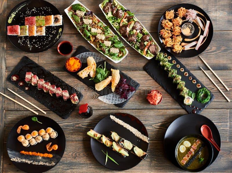 Tj?nande som sushirullar och annan traditionell asiatisk mat f?r japan och p? en tabell royaltyfri bild