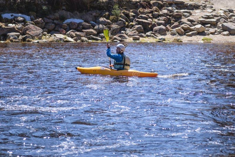 04 2019 tjeck En man på en bergflod kopplas in, i rafting En flicka kayaking ner en bergflod flicka i en kajak, sidosikt arkivbild