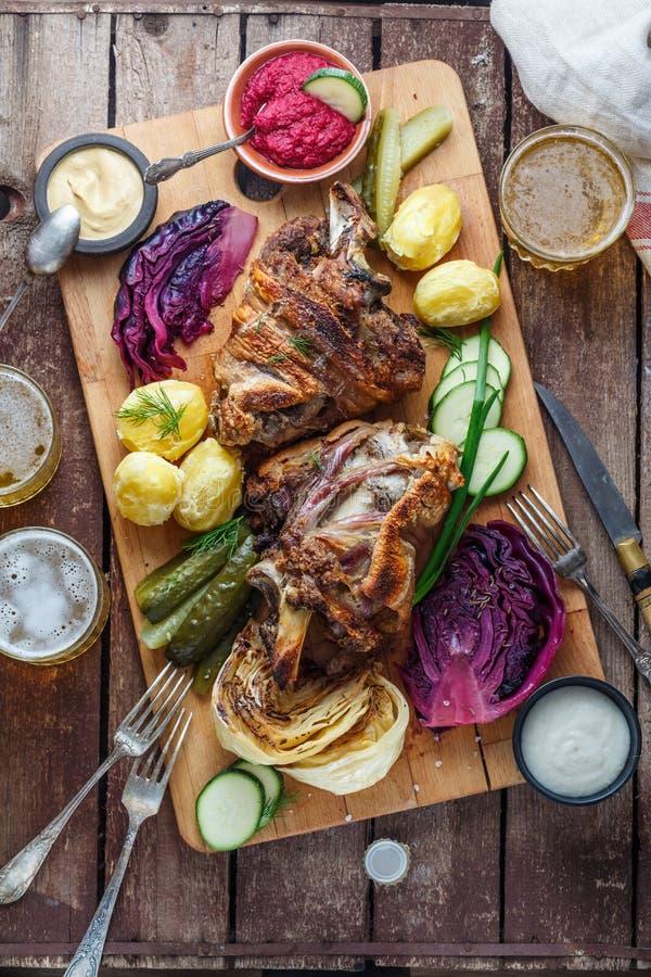 Tjecken bakade grisköttknukle med potatisen, knipor och öl, bästa sikt arkivbilder