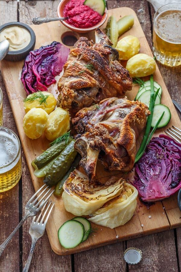Tjecken bakade grisköttknukle med potatisen, knipor och öl, bästa sikt royaltyfria bilder