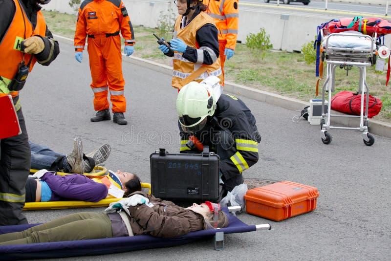 TJECKIEN PLZEN, 30 SEPTEMBER, 2015: Brandmän och räddare som tar bort sårat på en bår av bilolyckan royaltyfri fotografi