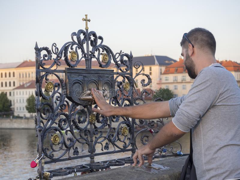 Tjeckien Prague, September 8, 2018: Turist för ung man som trycker på den fallande prästen Saint John av Nepomuk på bronsplaqen royaltyfria foton