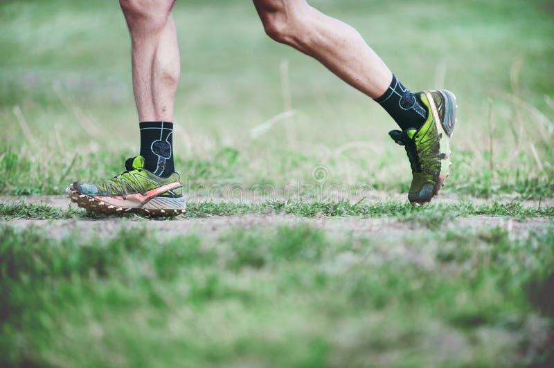 TJECKIEN SLAPY, Oktober 2018: Slingagalningar kör konkurrens Ben av löparen i gröna Salomon Running Shoes royaltyfria bilder