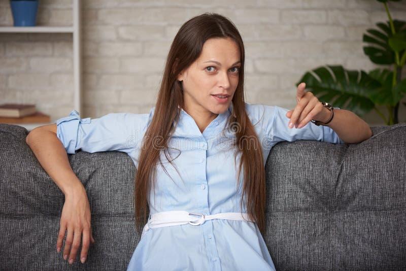 tjejen pekar finger åt dig när du sitter på en soffa hemma royaltyfria foton