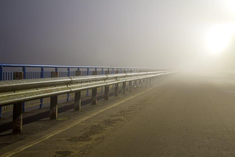 Tjock dimma över den tomma vägen på natten royaltyfri bild