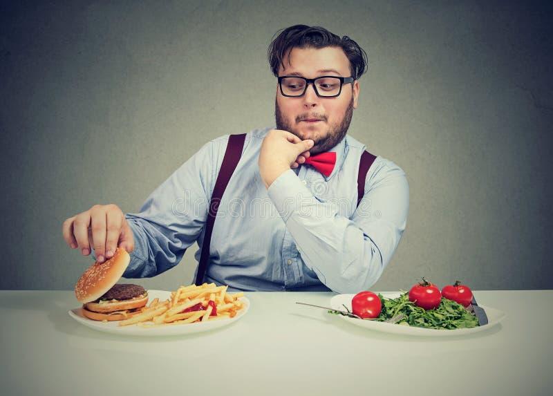 Tjock man som kräver den läckra hamburgaren fotografering för bildbyråer