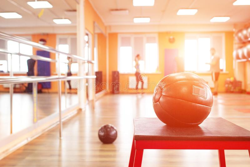 Tjock sjukligt fet grabb samman med den personliga slanka lagledaren att göra fysiska fjantar i idrottshall Fet manutbildning med royaltyfria bilder