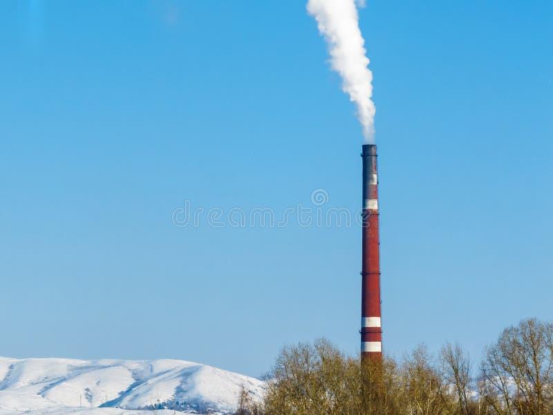 Tjock vit rök kommer ut ur det röda röret av fabriken mot en klar blå himmel, snöig berg och treetops arkivbilder