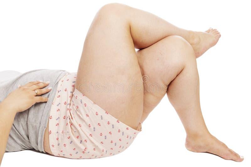 Tjocka kvinnliga ben i kortslutningar, närbild som isoleras på vit bakgrund arkivfoto