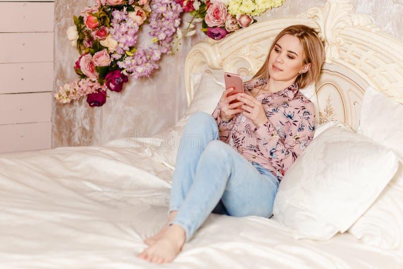 Tjugo-år-gammal gullig Caucasian kvinna som ligger på sängen och ser smartphonen royaltyfri fotografi