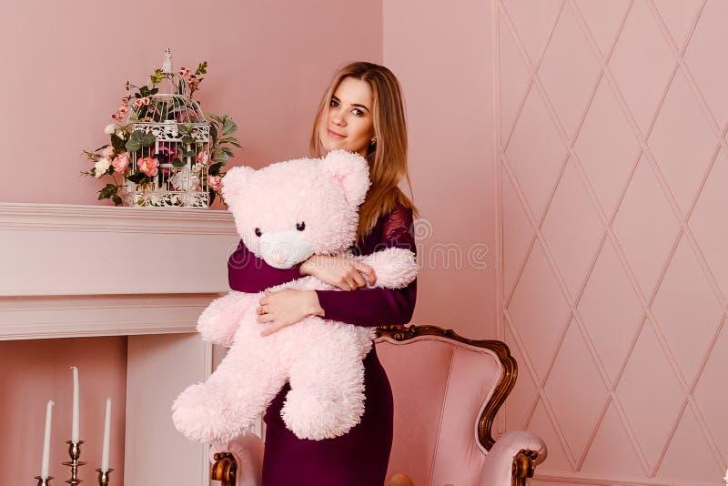 Tjugo-år-gammal kvinna i en Bourgogneklänning som rymmer en stor rosa nallebjörn royaltyfria foton