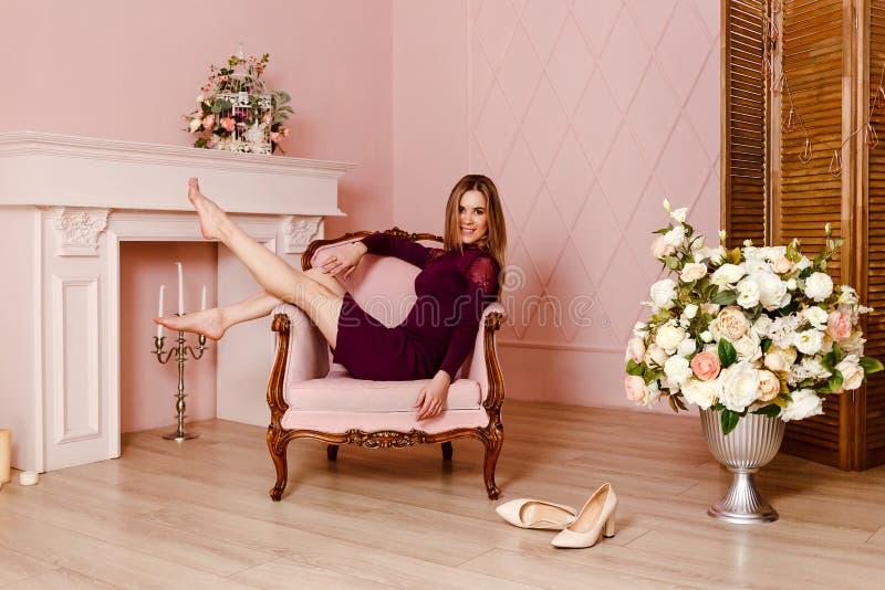 Tjugo-år-gammal lycklig härlig kvinna som sitter i en rosa stol med hennes ben upp inomhus arkivbild