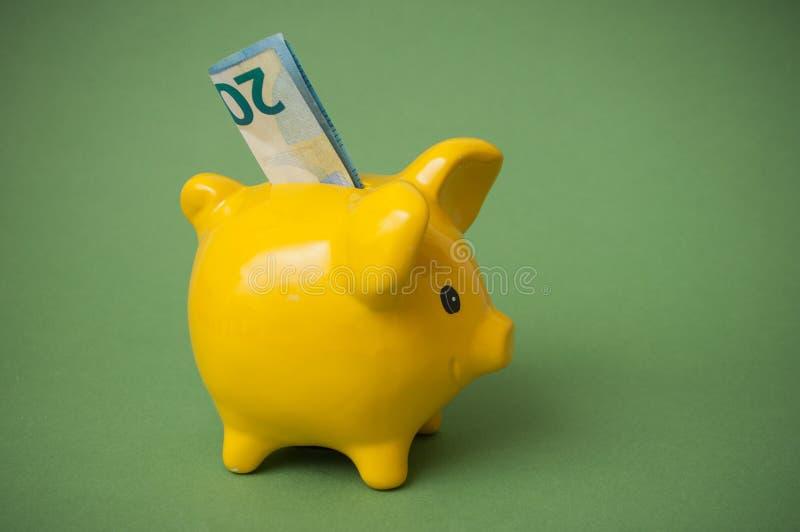 tjugo euro sedel i den gula spargrisen på gul bakgrund royaltyfri fotografi