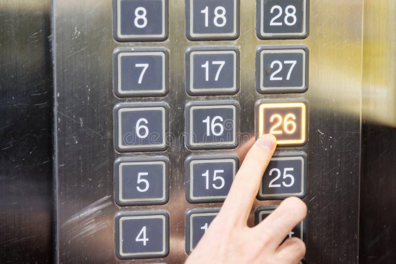 (tjugosex) hissknapp för golv 26 med det ljusa och driftiga fingret royaltyfria foton