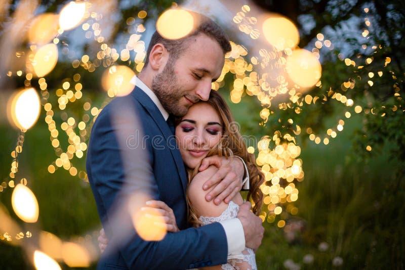 Tjusade nygifta personer omfamnar försiktigt Br?llopceremoni i natur Ljusen av den elektriska girlanden exponerar br?llopet royaltyfri bild