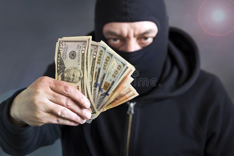 Tjuv i balaclava med dollar i hand korruption _ bedrägeri arkivfoton