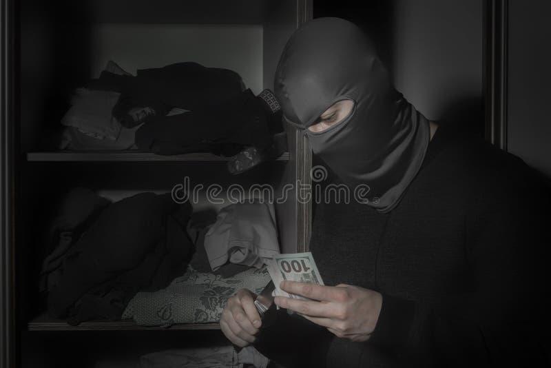 Tjuv i en maskering med en kniv och med ficklampast?ldpengar fr?n rummet royaltyfri fotografi