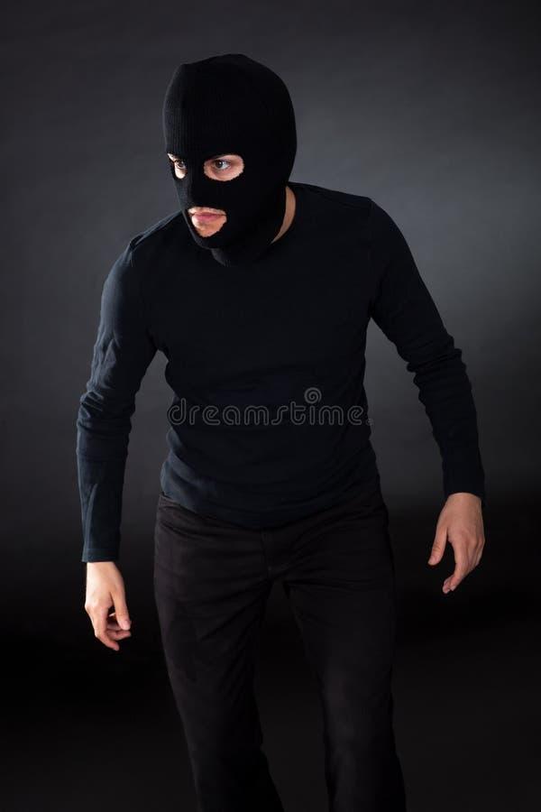 Tjuv som ha på sig en balaclava arkivfoto