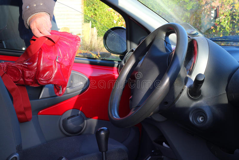 Tjuv som stjäler en handväska från ett medel eller en bil. arkivfoton