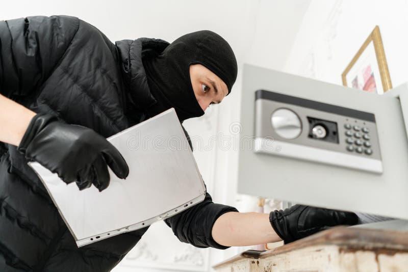 Tjuven öppnar det elektroniska kassaskåpet Inbrottstjuven begår ett brott i lyxig lägenhet med stuckaturen Tjuv med svart royaltyfri bild