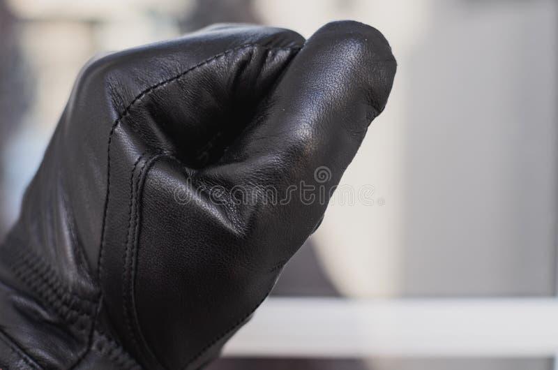 Tjuven, bärande svarta handskar, knackar på fönstret av huset för att kontrollera, om ägarna är hemmastadda royaltyfri fotografi