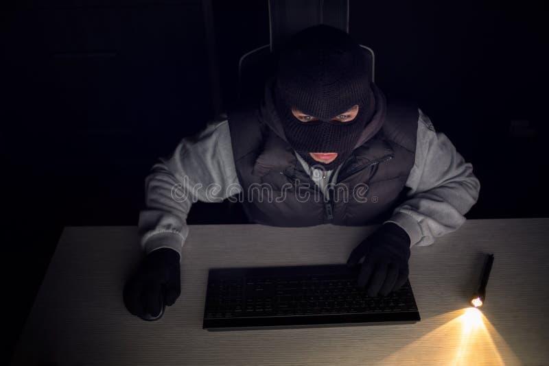 Tjuven hackermaskinskrivning på nyckel- bräde i mörker royaltyfri foto
