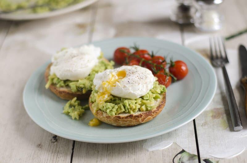 Tjuvjagad ägg och avokado på rostat bröd arkivbilder
