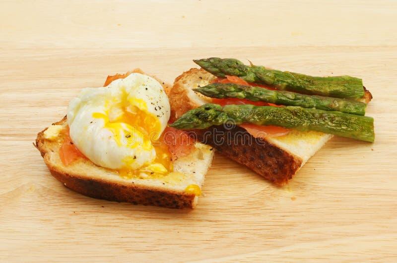 Tjuvjagad ägg rökt lax och sparris arkivfoton