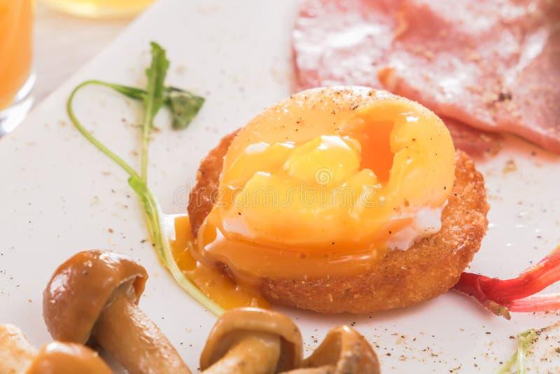 Tjuvjagat ägg med en flödande äggula på ett frasigt rostat bröd med champinjoner, skinka och gräsplaner Ny fruktsaft, sås royaltyfri fotografi