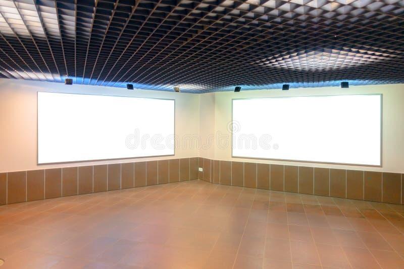 ?tl?je upp Två stora tomma vita affischtavlor på väggen inom byggnad royaltyfria foton