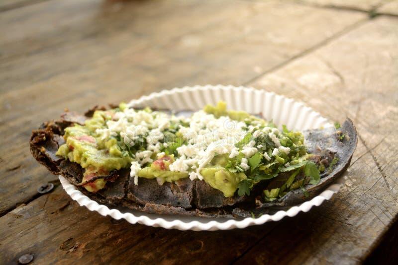 Tlacoyos mexicanos, um prato feito com milho azul e enchido com os feijões ou as favas fritadas, similares ao gordita mexicano, c foto de stock royalty free