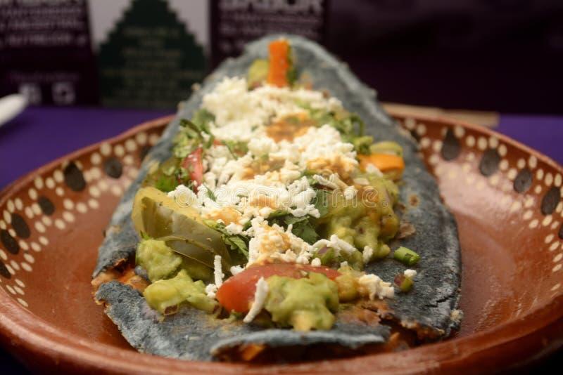 Tlacoyos mexicanos, un plato hecho con maíz azul y llenado de las habas fritas o de las habas, similares al gordita mexicano, con imagen de archivo libre de regalías