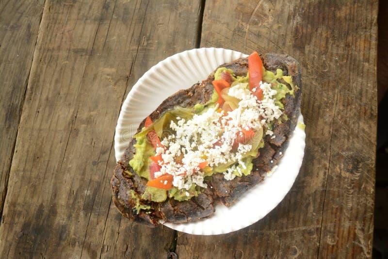 Tlacoyos mexicanos, un plato hecho con maíz azul y llenado de las habas fritas o de las habas, similares al gordita mexicano, con imágenes de archivo libres de regalías