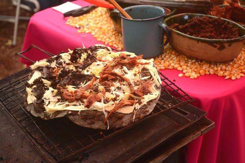 Tlayuda die in het fornuis of anafre in Mexico, heerlijke reusachtige tortilla met bonen, Oaxaca-kaas en schokkerig rundvlees wor stock fotografie