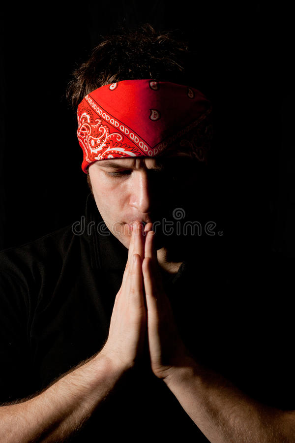 Tmotional portrait of a young praying man. Emotional portrait of a young man praying in the darkness royalty free stock photo