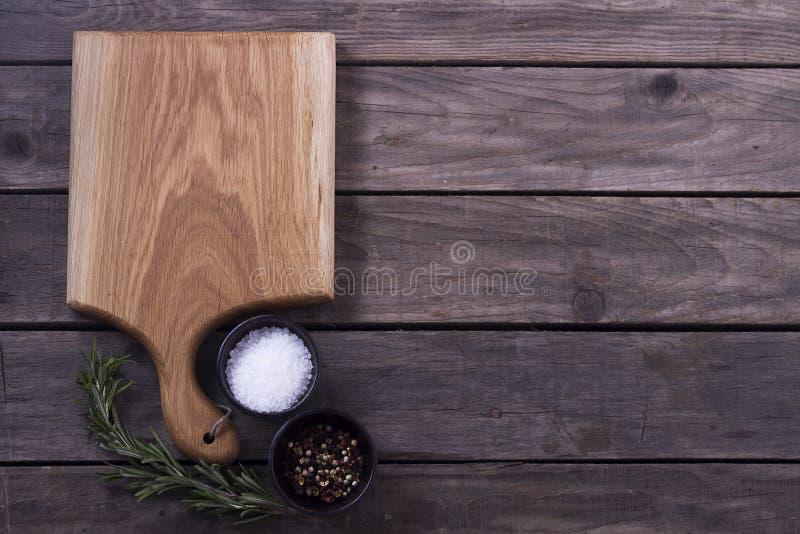 Tnąca deska, rozmaryny i pikantność na starym drewnianym stole, kosmos kopii Pojęcie dla restauracyjnego cukiernianego bistro men obrazy royalty free