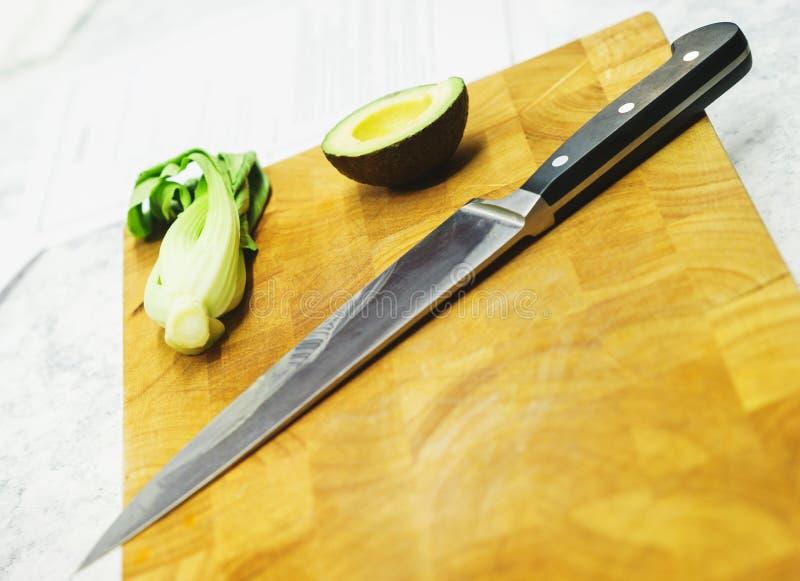 Tnącej deski i noża zakończenie na kuchennym stole Avocado i zielenie obraz royalty free