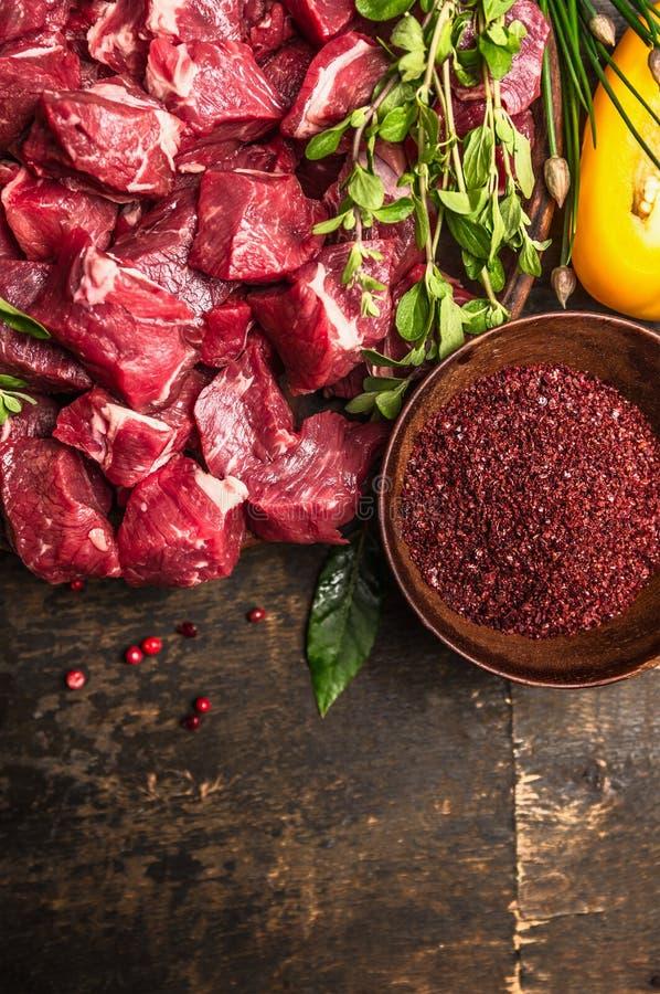 Tnący surowy mięso z pikantność i świeżymi ziele, składniki dla goulash kucharstwa na nieociosanym drewnianym tle, odgórny widok obraz stock