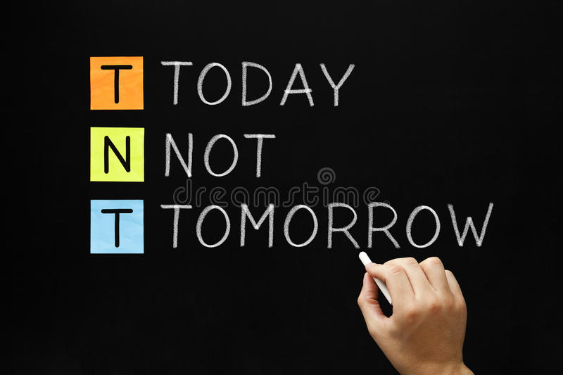 TNT - Today Not Tomorrow. Hand writing Today Not Tomorrow with white chalk on blackboard stock images