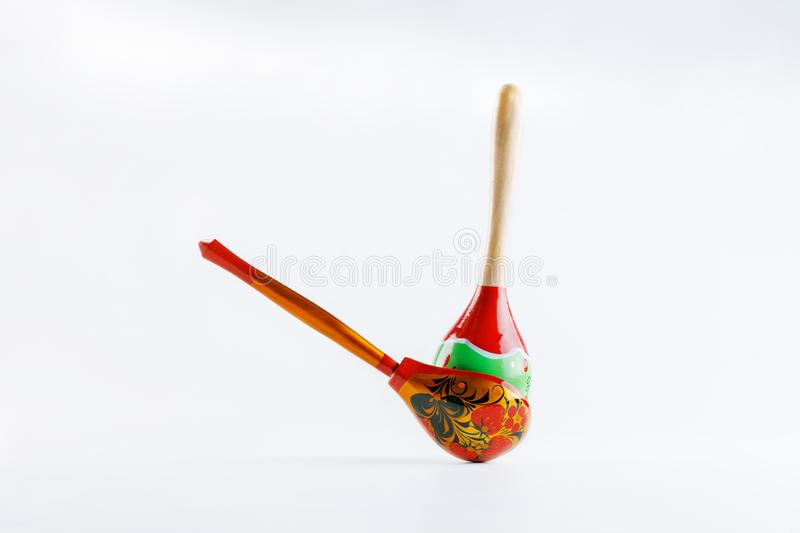 A wooden spoon with a floral ornament in the traditional Russian folk style and a Mexican maracas with a traditional pattern on a royalty free stock image